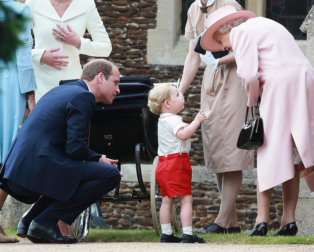 Prince George of Cambridge talks to Queen Elizabeth II outside the Church of St Mary Magdalene on the Sandringham Estate for the Christening of Princ