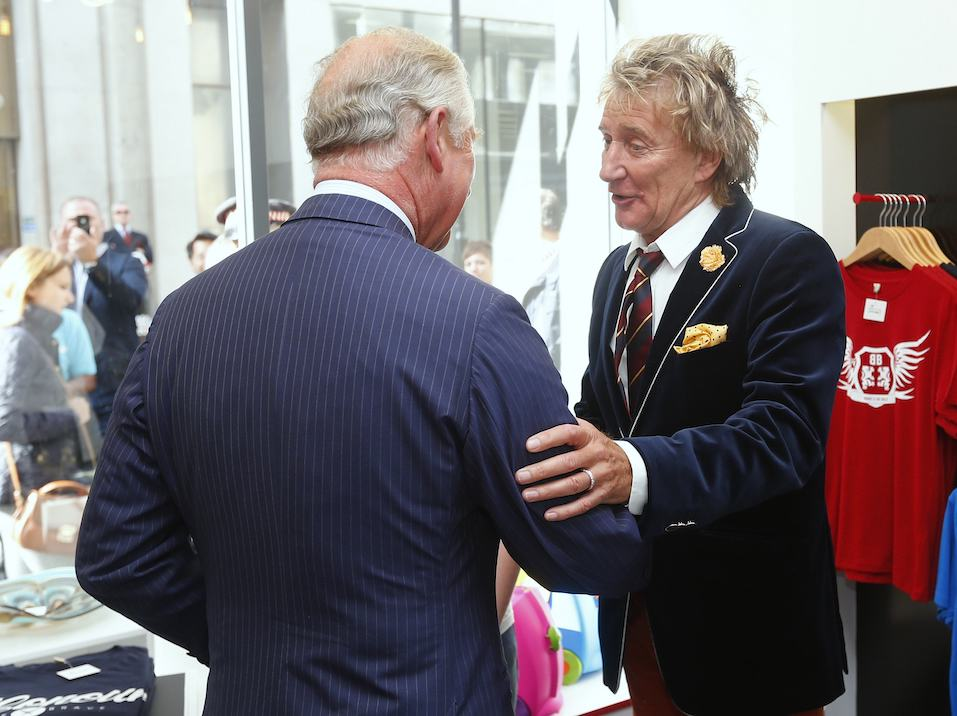 Rod Stewart (R) apologises to Prince Charles, Prince of Wales after arriving late for the opening of The Prince's trust 'Tomorrow's Shop'