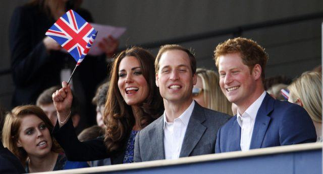 Kate Middleton waving a flag while sitting with her family in a balcony.
