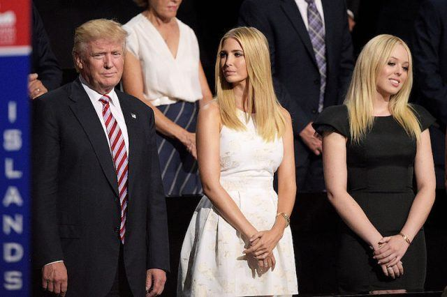 Tiffany Trump posing with Donald Trump and Ivanka Trump.