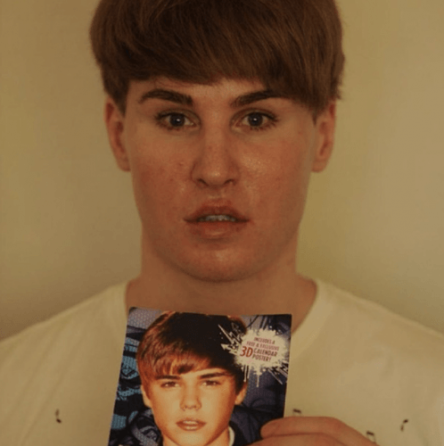 Toby Sheldon holding a photo of Justin Bieber.