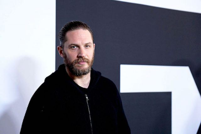 Tom Hardy wears a black hoodie on a red carpet.