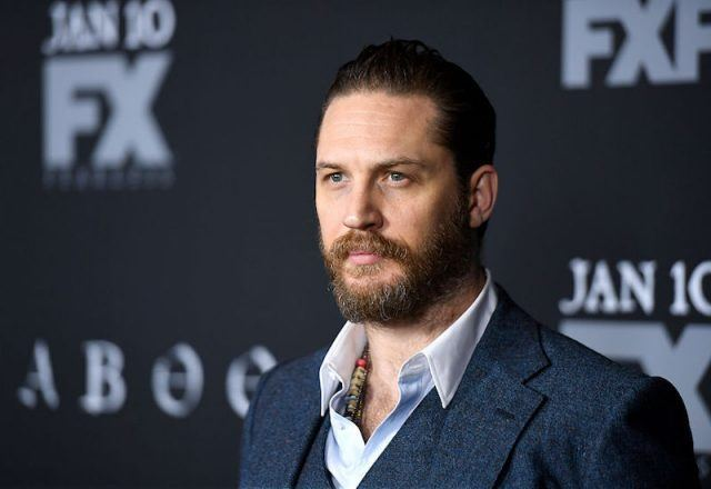 Tom Hardy posing on a red carpet.