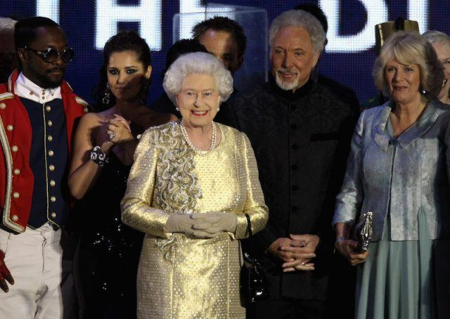 Queen Elizabeth stands and smiles with Tom Jones.
