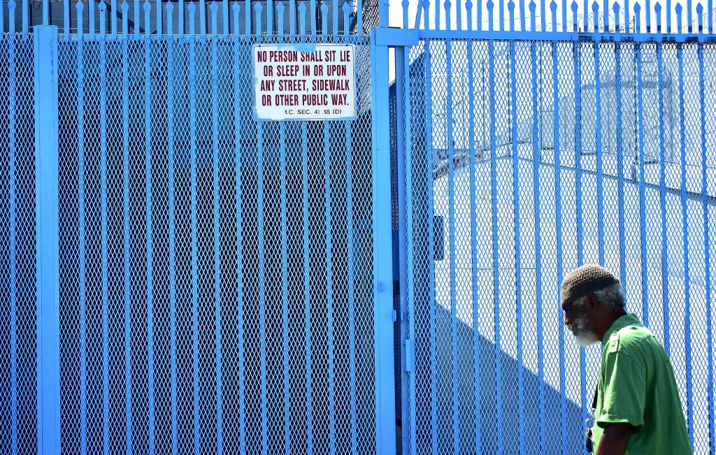 A man walks past a sign posting the ordinance which led to the explosion of tents housing the homeless on Los Angeles streets