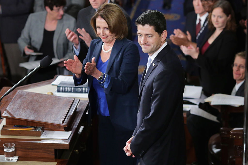 Speaker-elect of the House Paul Ryan and Minority Leader Nancy Pelosi applaud on the floor of the House chamber