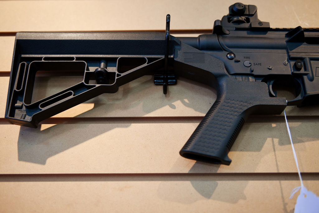 A bump stock installed on an AR-15 rifle
