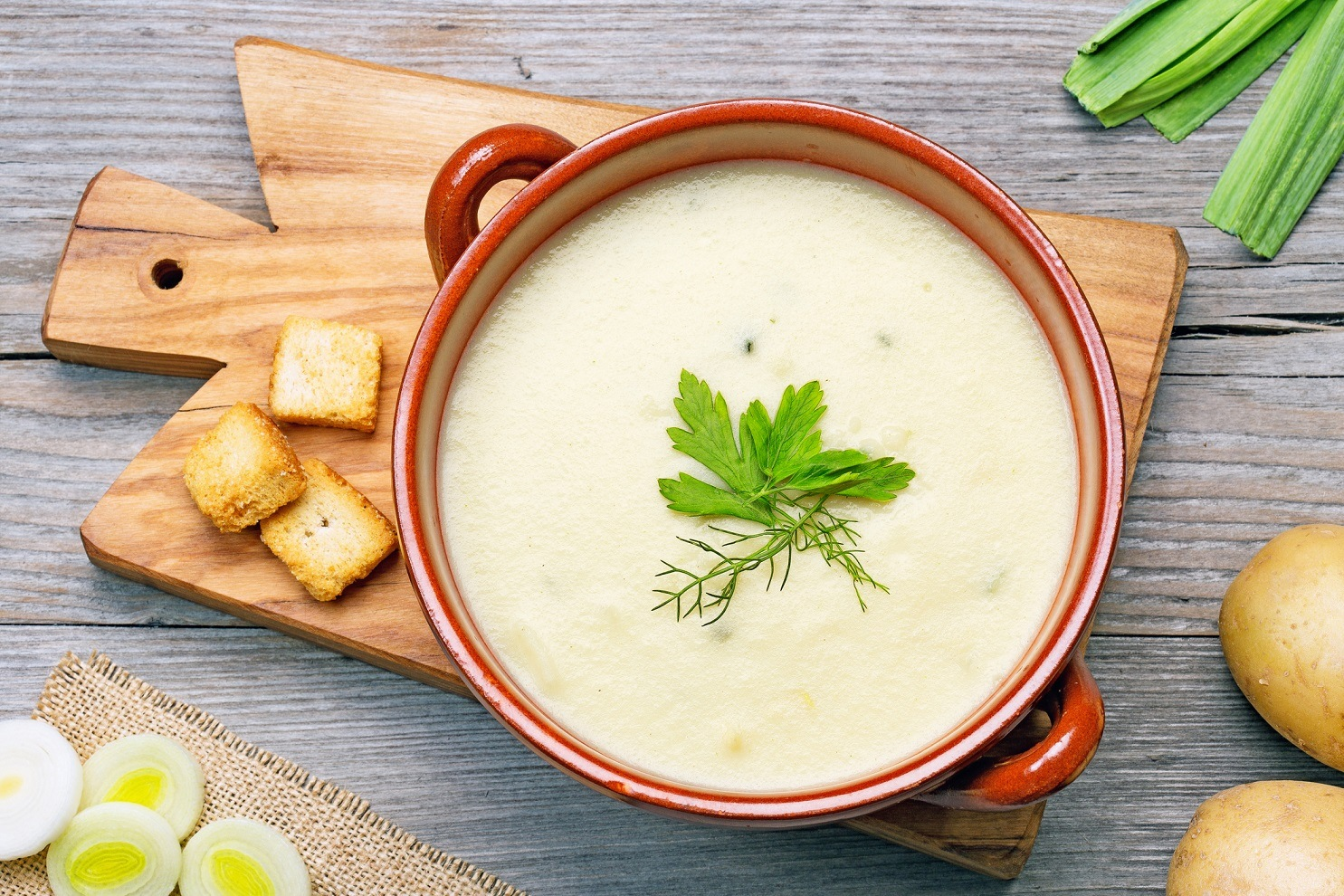 leek and potato soup and ingredients on wooden cutting board
