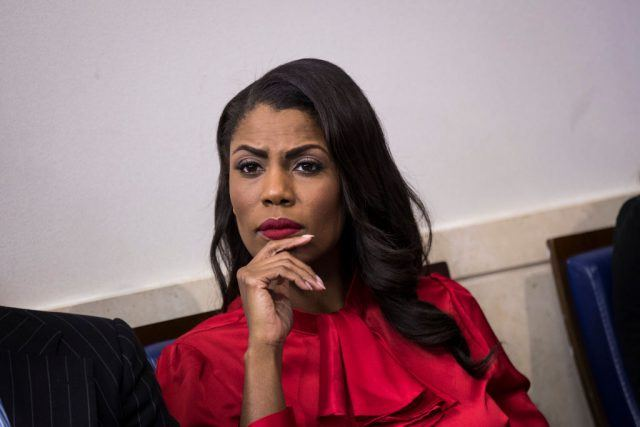 Omarosa Manigault sits in a red dress with her hand holding her chin.