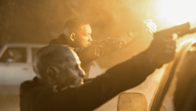 Will Smith and an alien aiming their weapons.