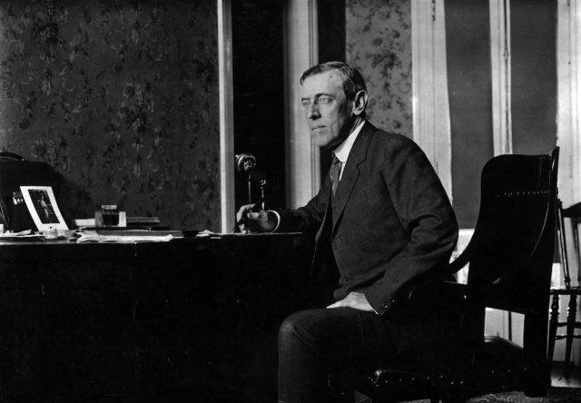 Woodrow Wilson sitting at a desk with a microphone.