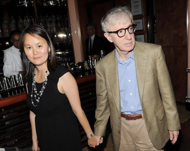 Woody Allen and Soon-Yi Previn holding hands while walking near a bar.