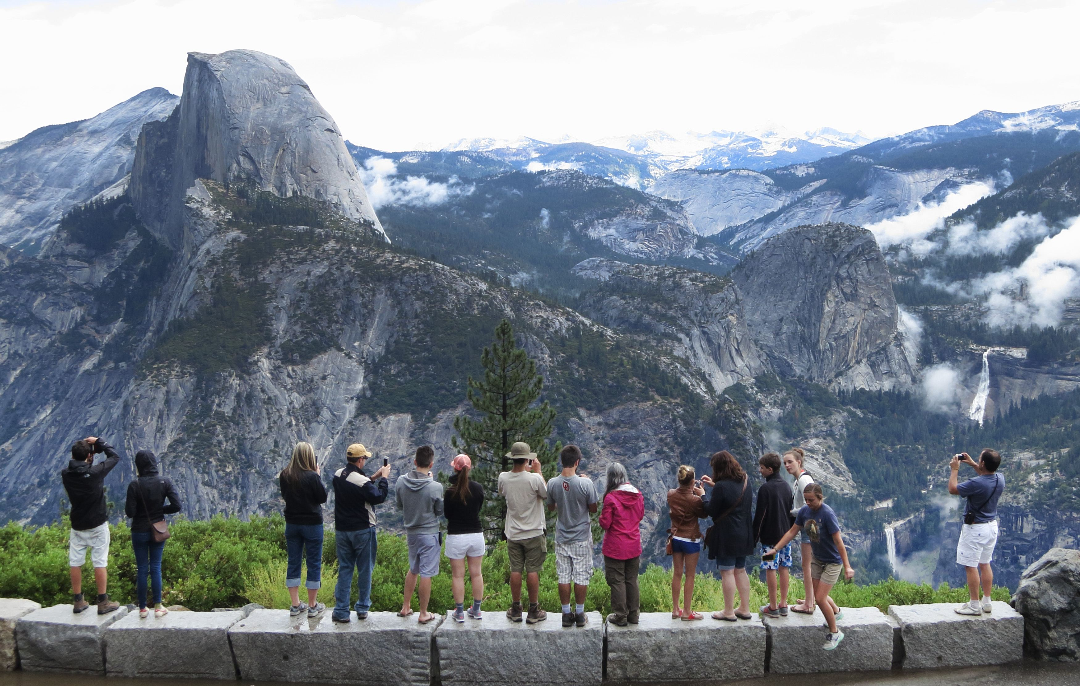 Visitors look out at Yosemite National Park from Glacier Point