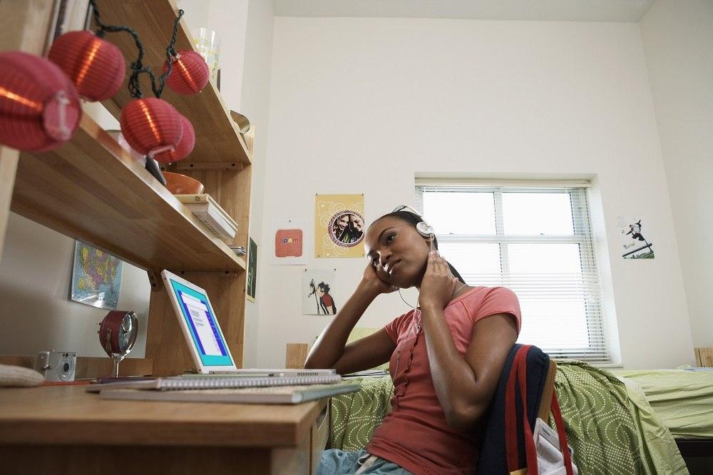 woman sitting at desk, wearing headphones