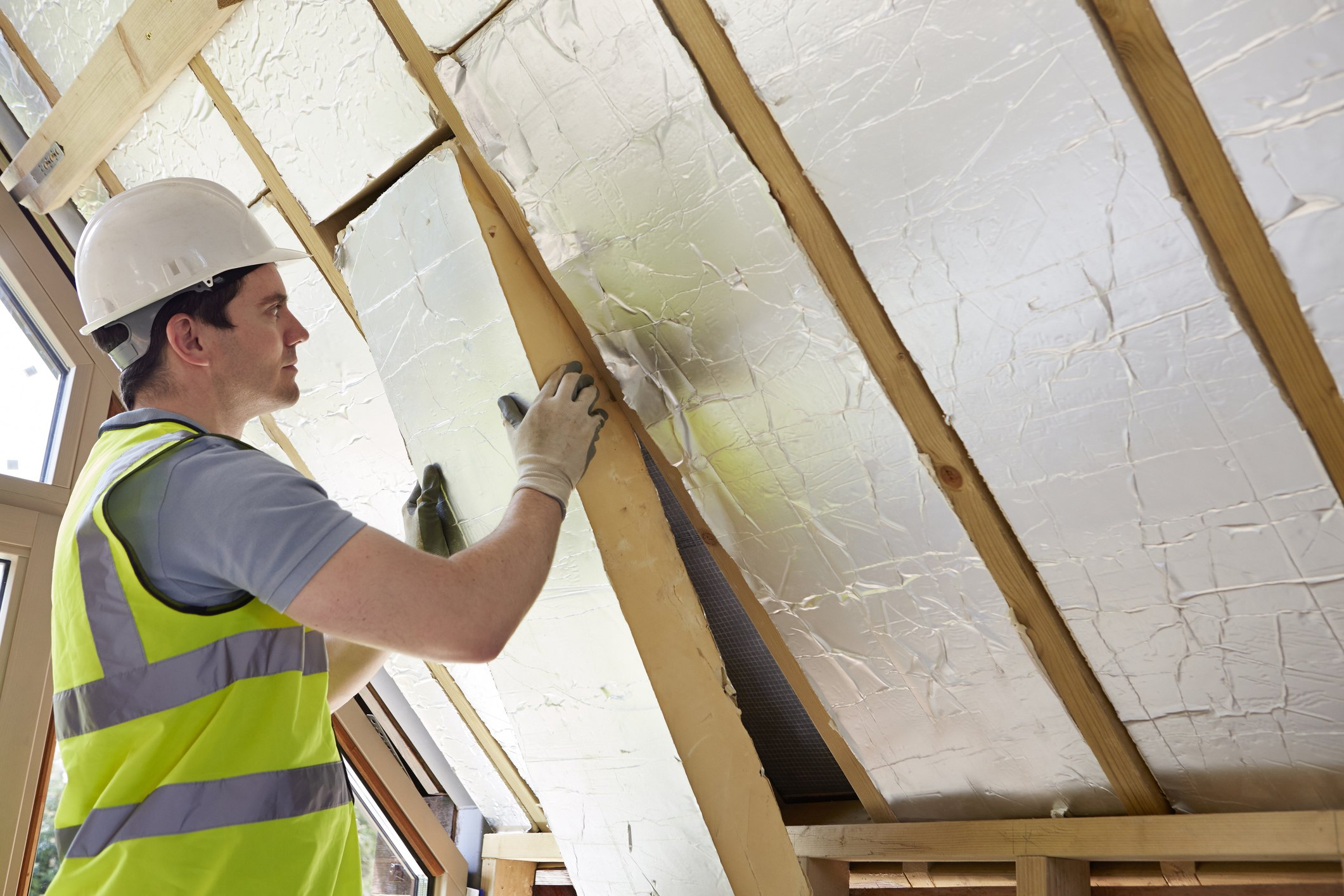 Builder Fitting Insulation Into Roof Of New Home