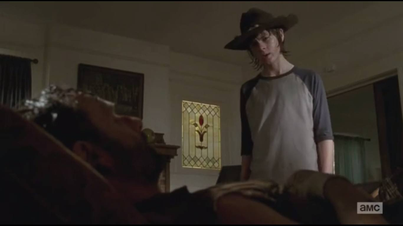 Carl stands above an injured Rick who lays in bed