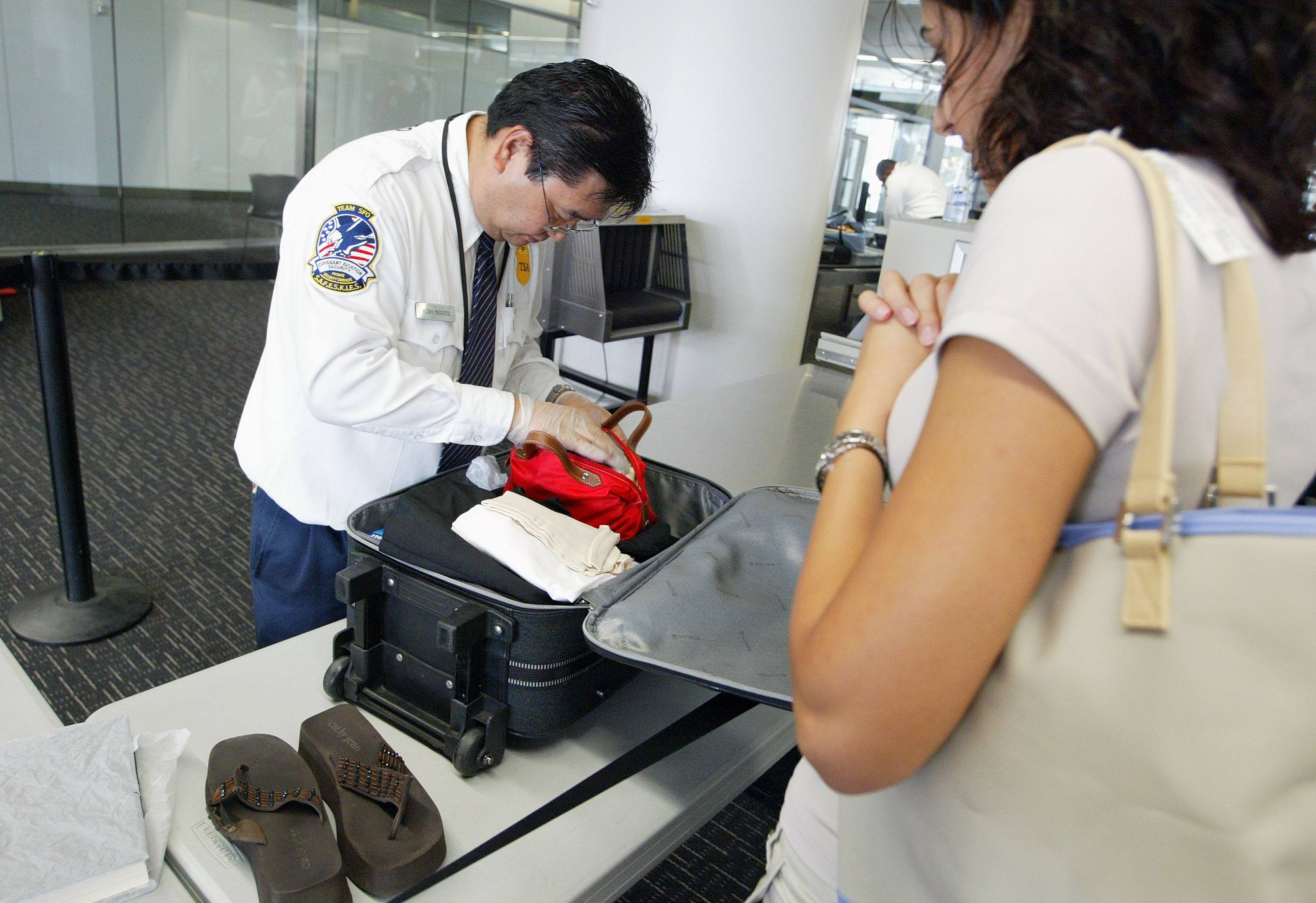 Airport security bag search by TSA agent