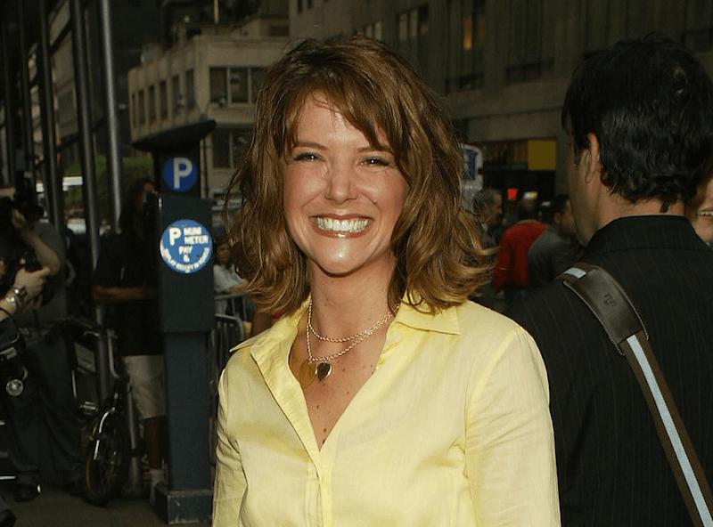 AJ Langer smiles in a yellow shirt