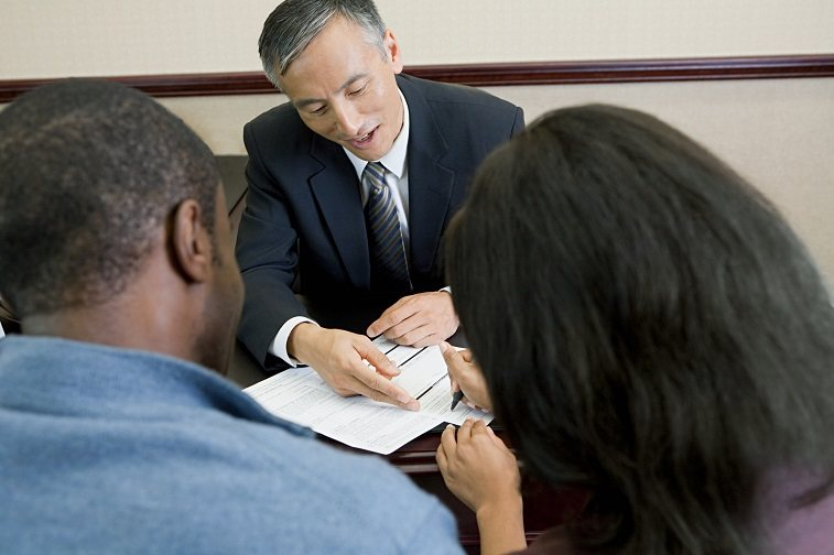 a Bank manager talking to a pair of customers