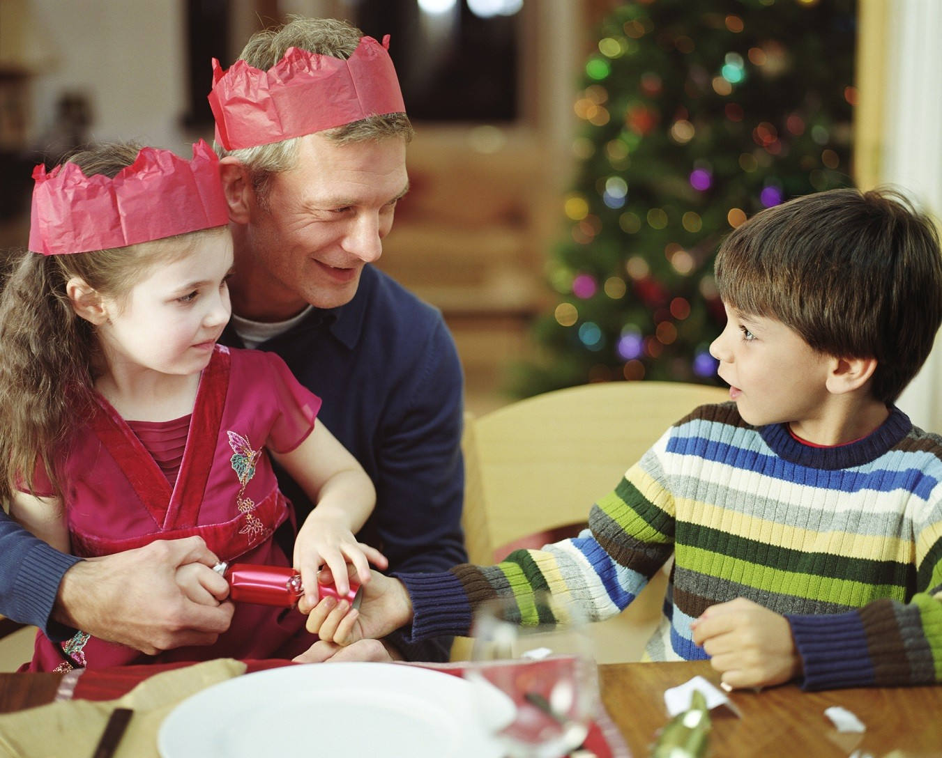 British Family at Christmas with crowns and cracker