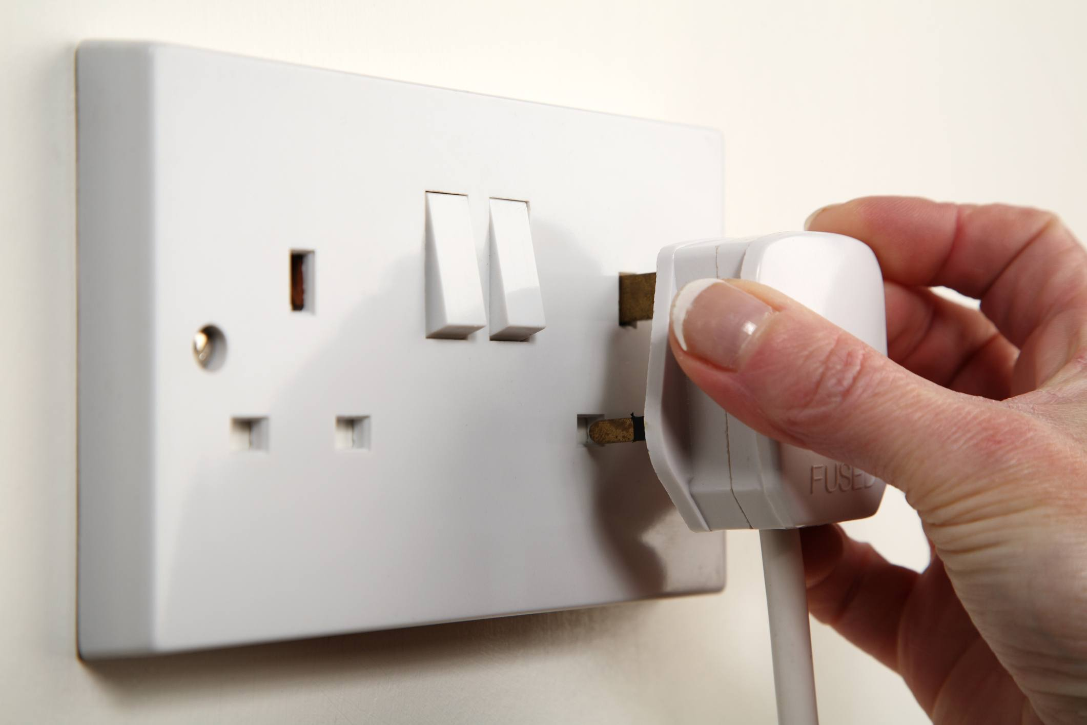 Hand plugging a plug into a grounded, British socket