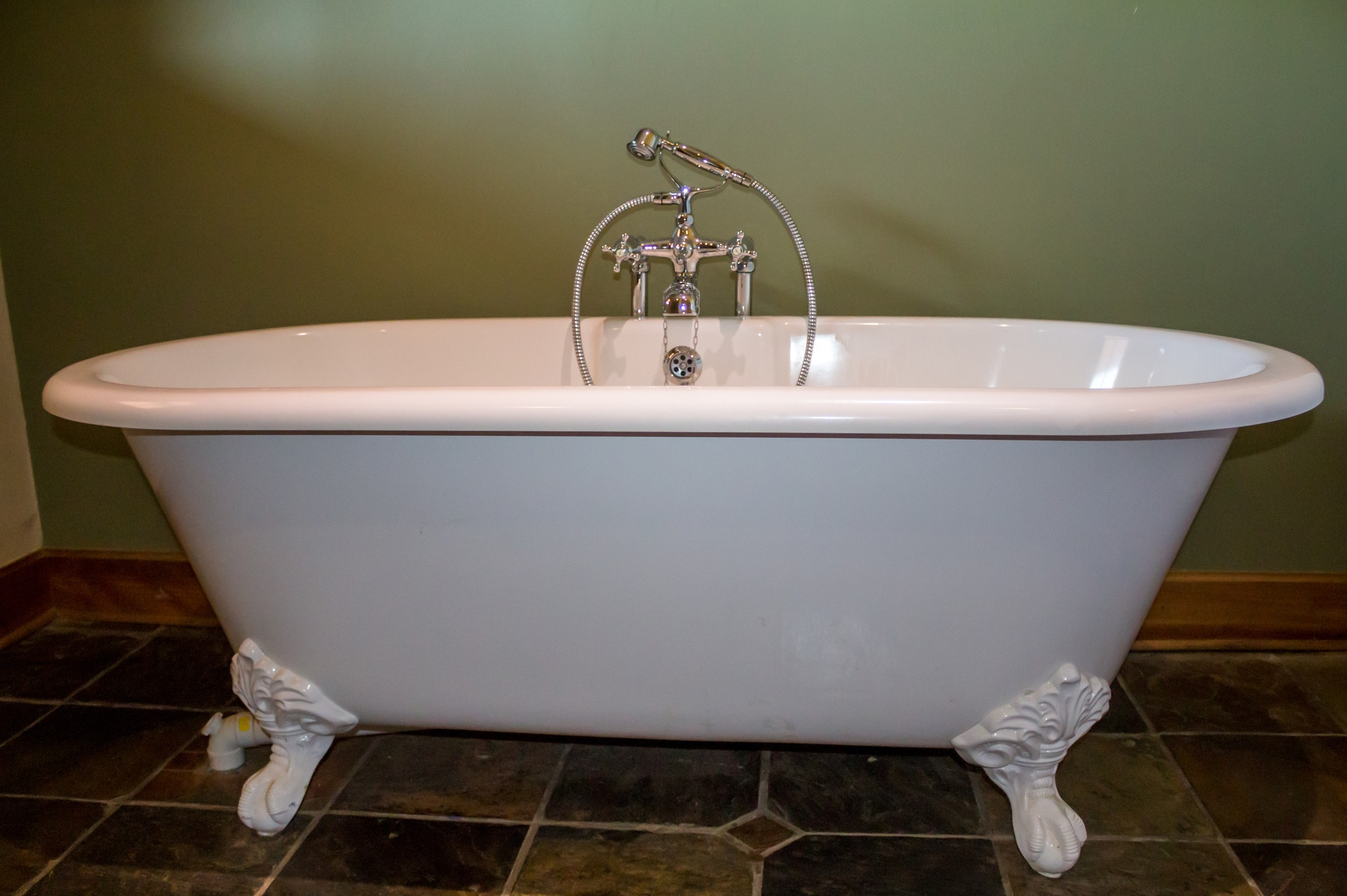 Claw foot bath tub in olive green bathroom