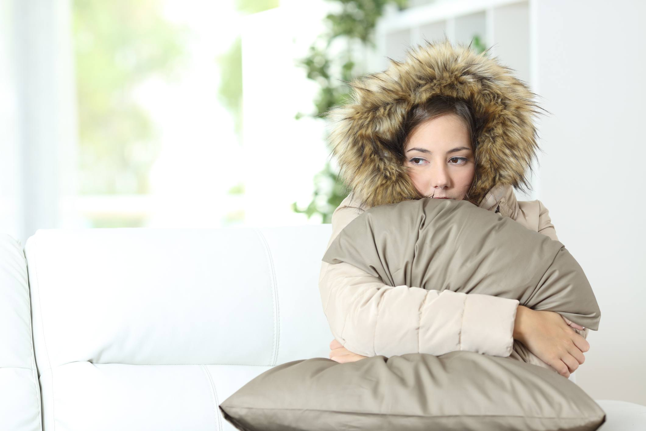 Cold Woman warmly clothed in a cold home