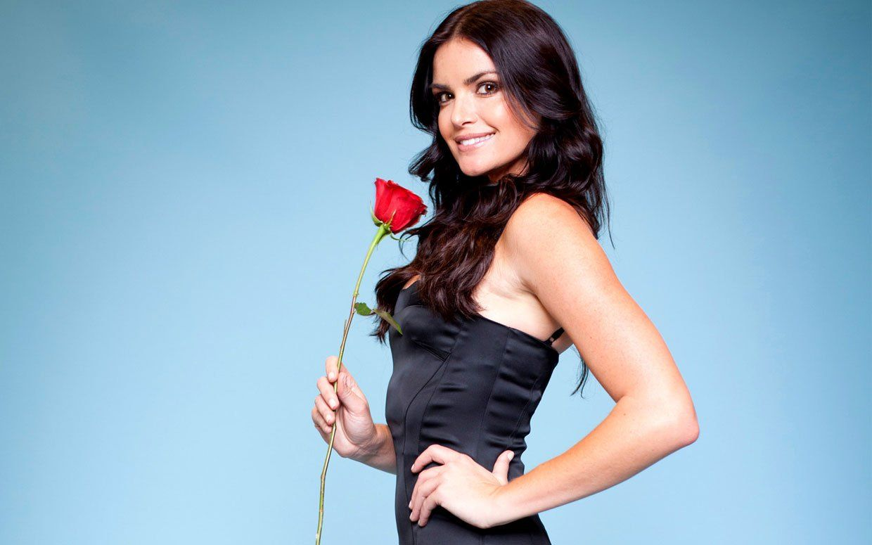 Courtney Robertson holds up a rose