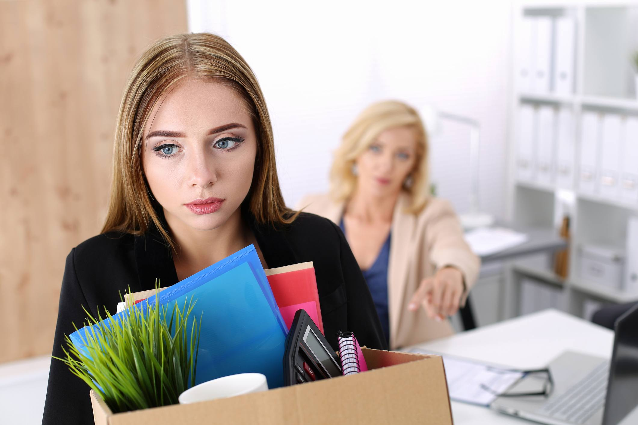 Fired or laid off worker leaving the office with a box of her things