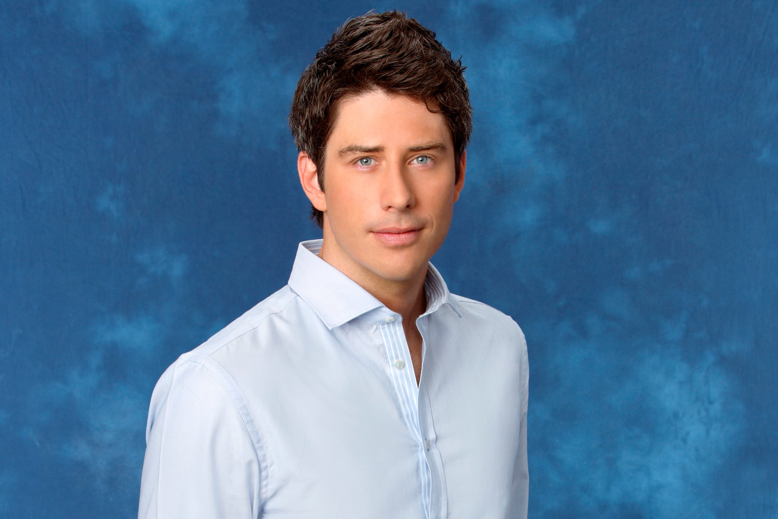 Arie Luyendyk Jr. poses in front of a blue background