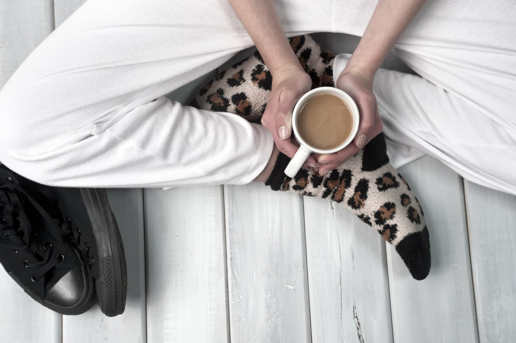 Girl sitting on floor with sweatpants and leopard socks