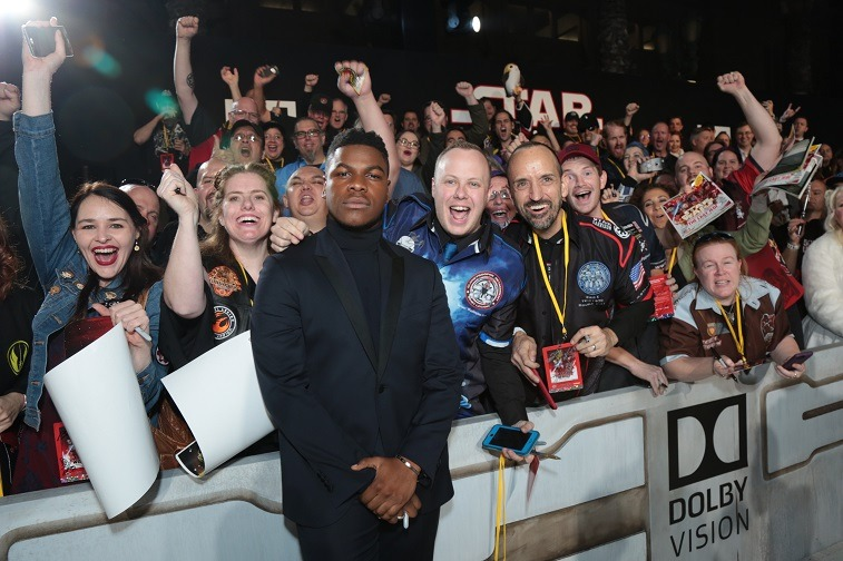 John Boyega poses with fans on the red carpet