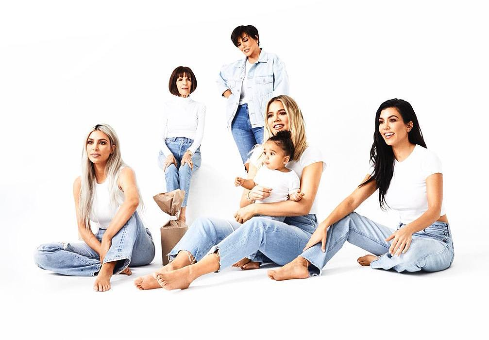 The Kardashian family members pose in jeans and a white shirt