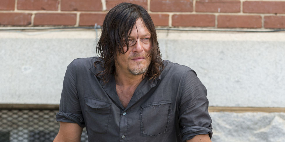 Daryl sits in front of a brick wall