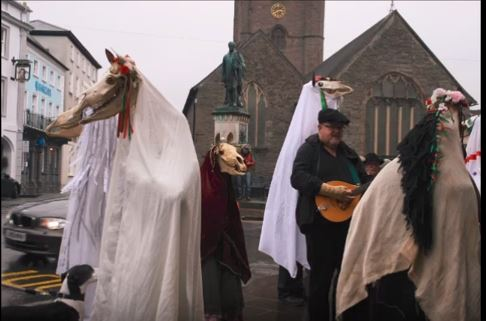 A group of Mari Wyd dance with revelers in Wales