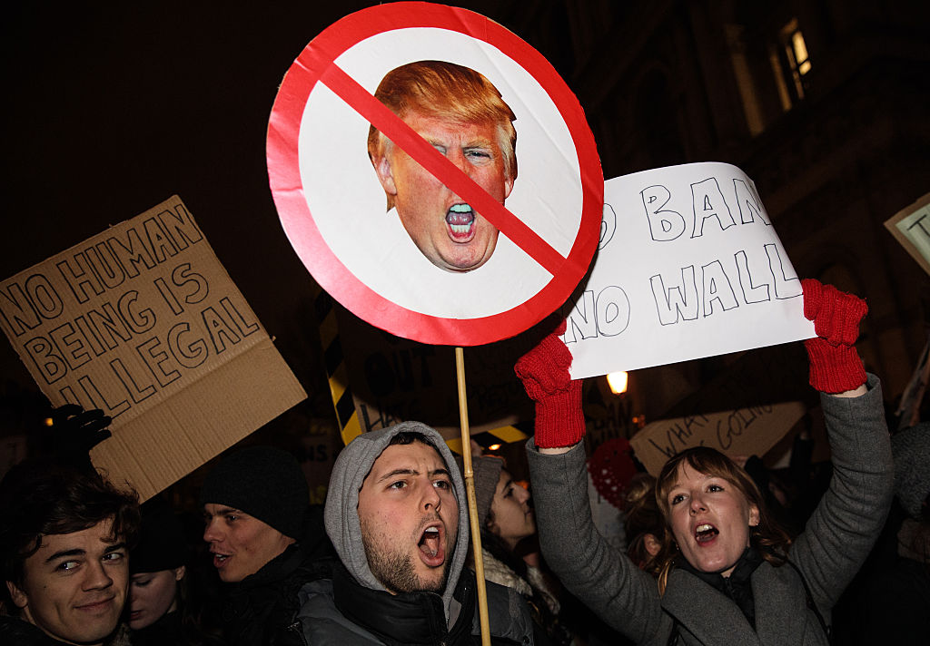 Protesters of Trump and his policies carrying signs and yelling.
