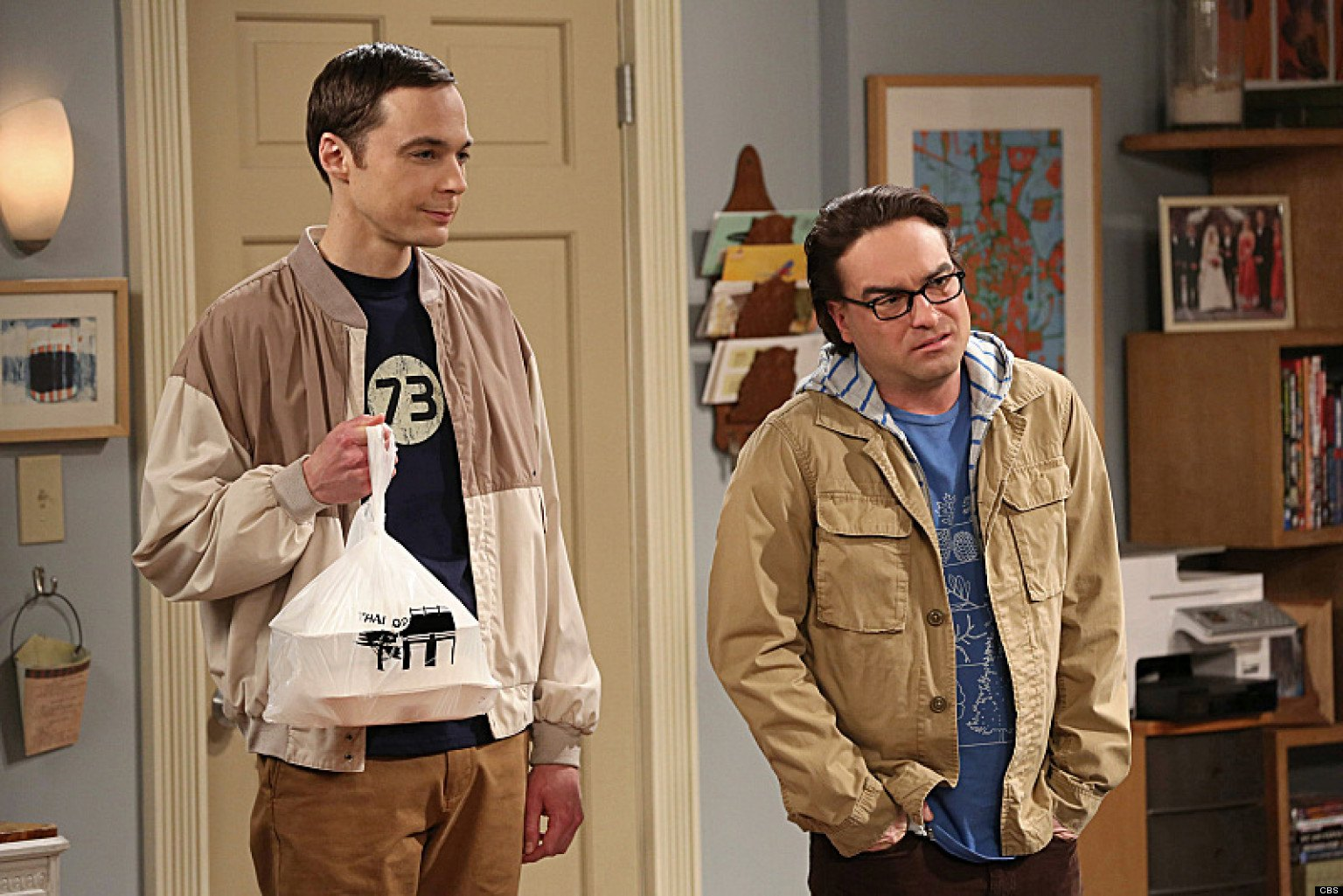 Sheldon and Leonard stand next to each other while holding bags of food