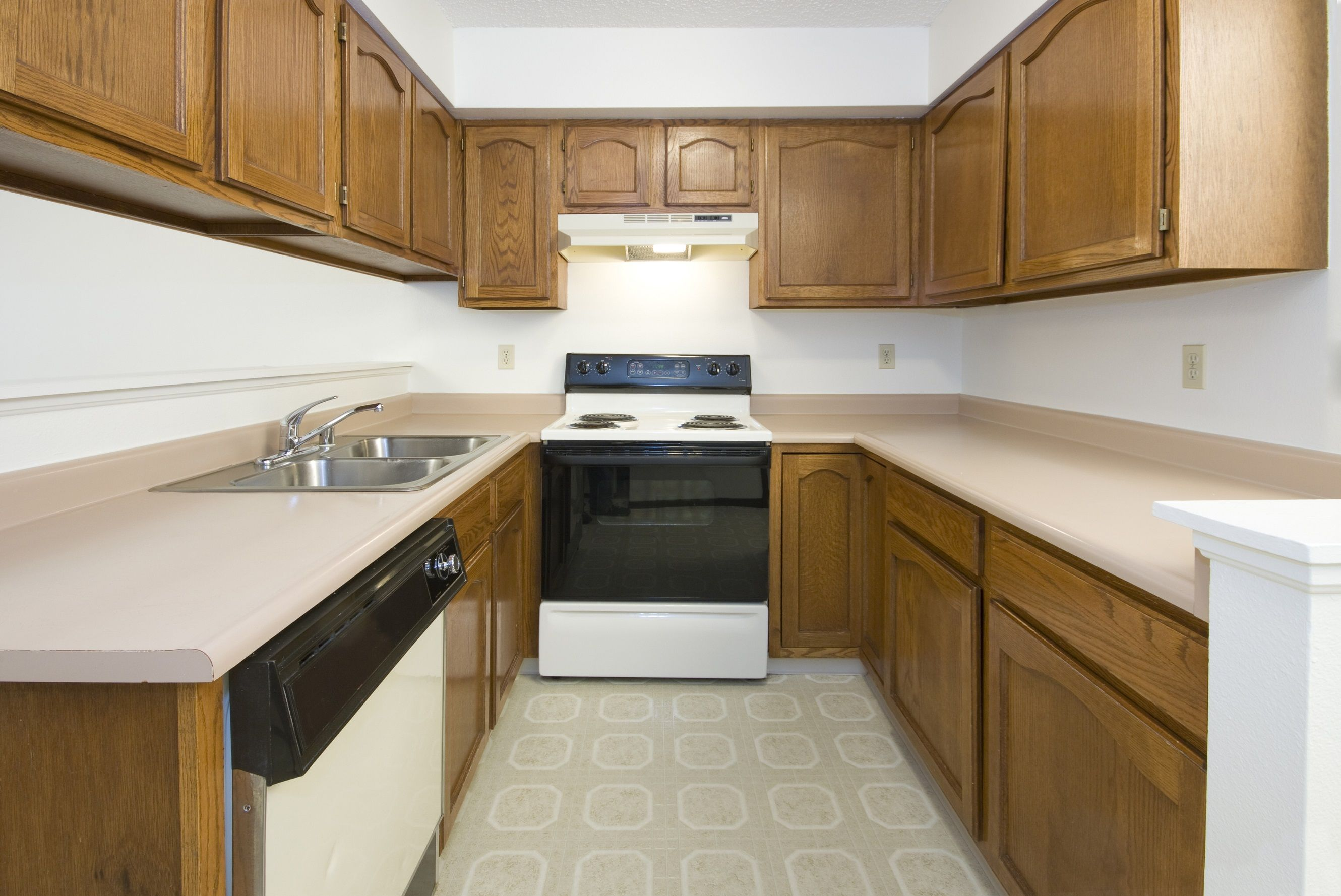 Old, dated kitchen with wood cabinets, laminate counters and old appliances