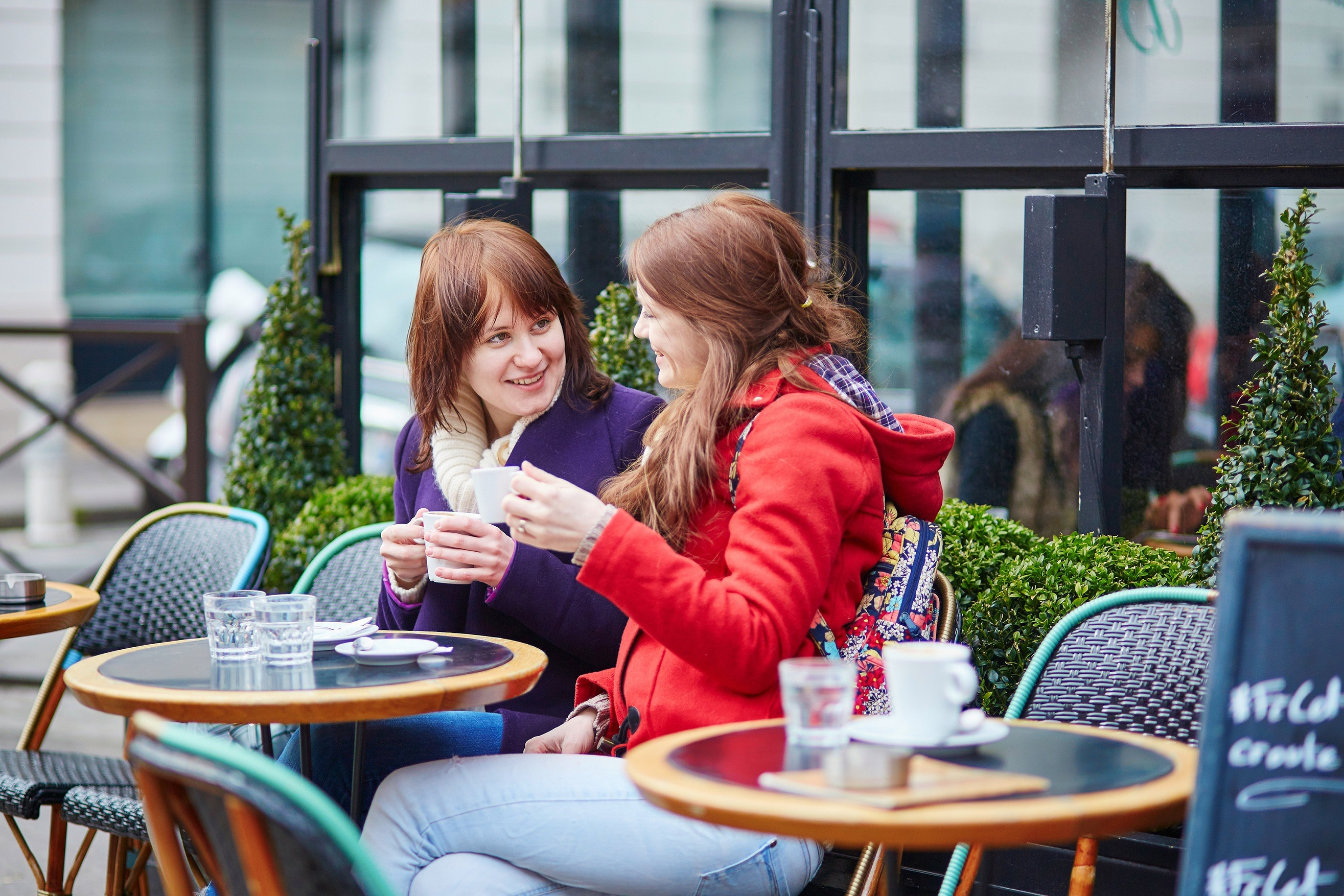 Two women sitting at a cafe table in Paris