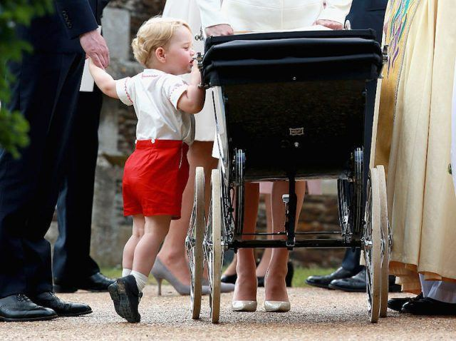 Prince George looking into a black stroller.