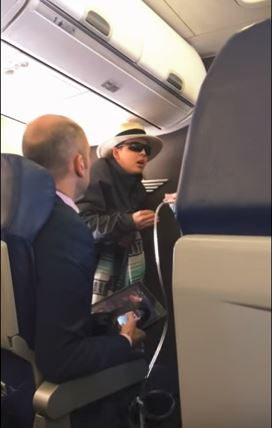 The woman began yelling as flight attendants tried to calm her