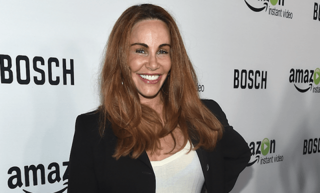Tawny Kitaen smiling while on a red carpet.