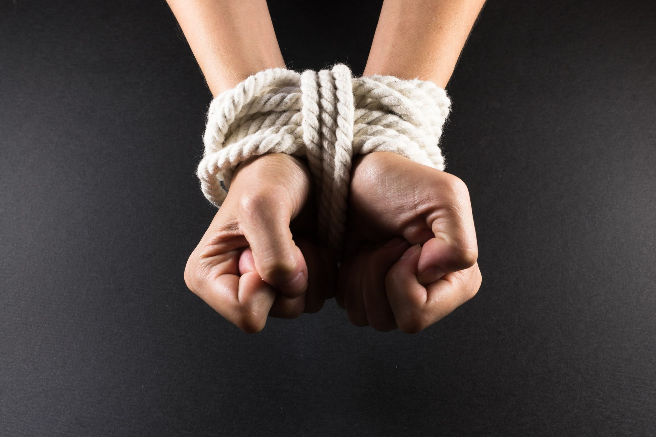 White hands bound with rope