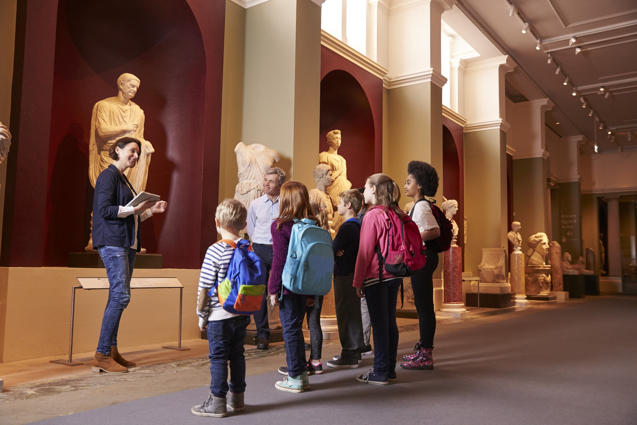 Children and tour guide discuss museum