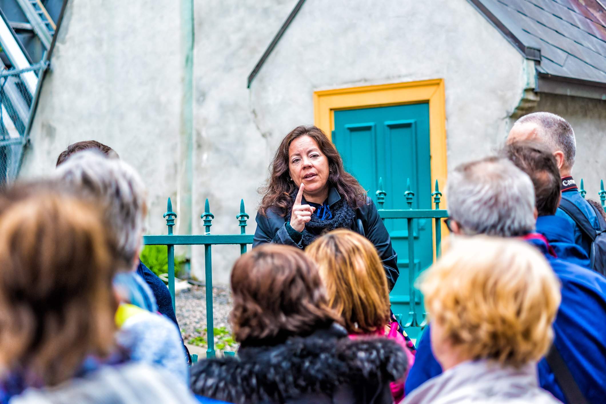Tour guide speaking to group in front of blue door