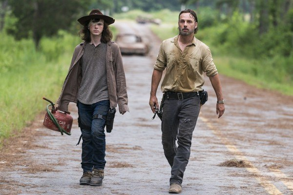 Rick and Carl walk next to each other down a road on The Walking Dead