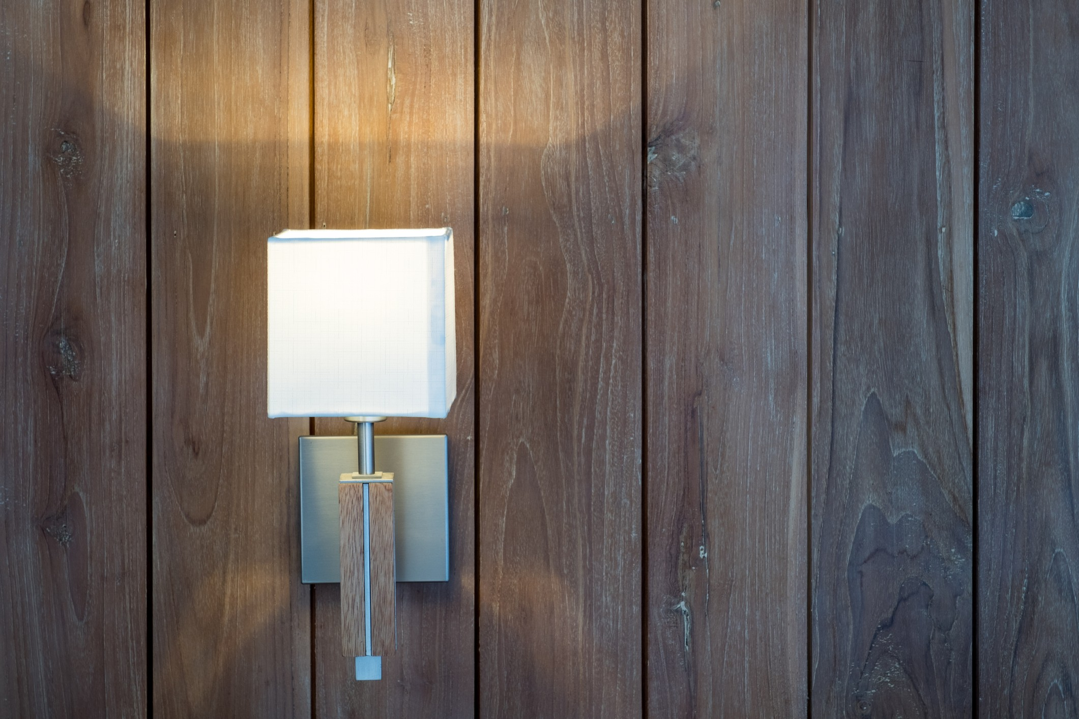 Square wall light on brown wood paneling