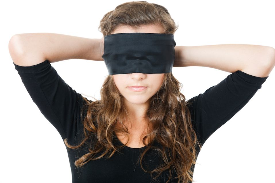Female tie her eyes with black ribbon