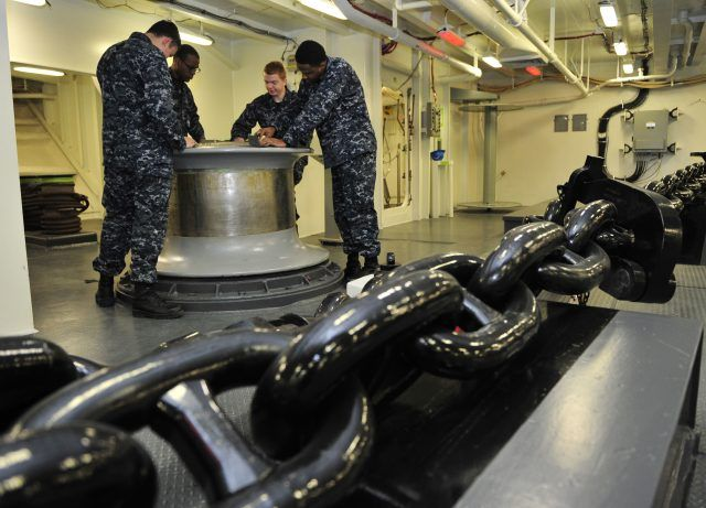 Deck Department Sailors assigned to Pre-Commissioning Unit Gerald R. Ford (CVN 78), polish the capstone inside the ship's forecastle.