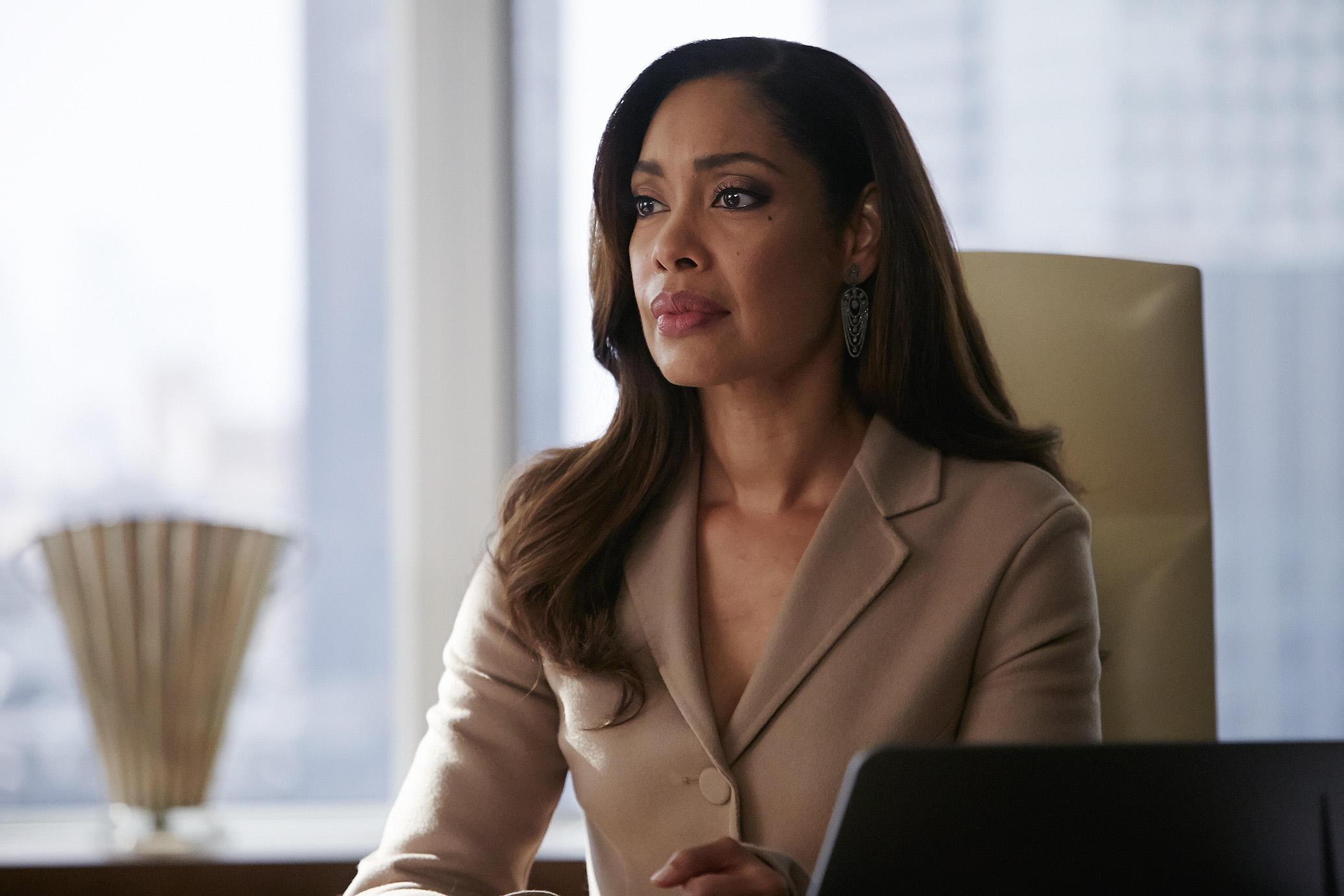 Gina Torres sits at a desk